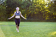 Woman skipping rope in park - JFEF00854