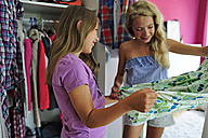 Two girls choosing clothes from wardrobe - ECPF00018