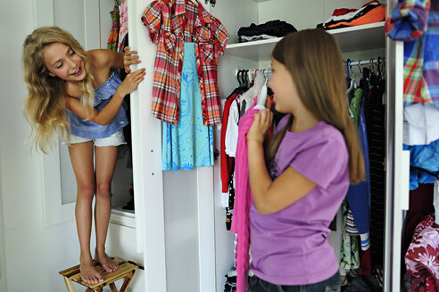 Two girls choosing clothes from wardrobe - ECPF00021