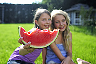 Two happy girls eating a water melon in garden - ECPF00030