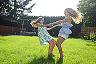 Two happy playful girls in garden - ECPF00033