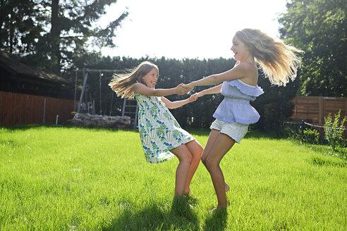 Two happy playful girls in garden - ECPF00033