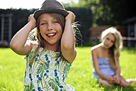 Happy playful girl putting on a hat in garden - ECPF00036