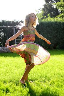 Happy girl wearing a dress in garden - ECPF00042