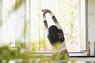 Woman stretching in kitchen - JOSF01243