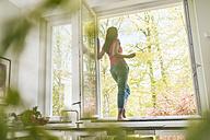 Woman standing in kitchen on windowsill - JOSF01246