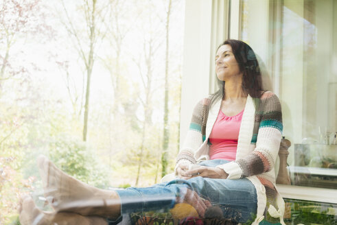 Confident woman at home looking out of window - JOSF01252