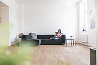 Woman at home using tablet on sofa - JOSF01258