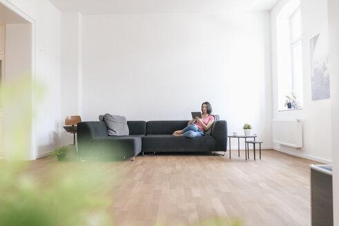 Woman at home using tablet on sofa - JOSF01258