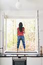 Woman standing in kitchen on windowsill - JOSF01261