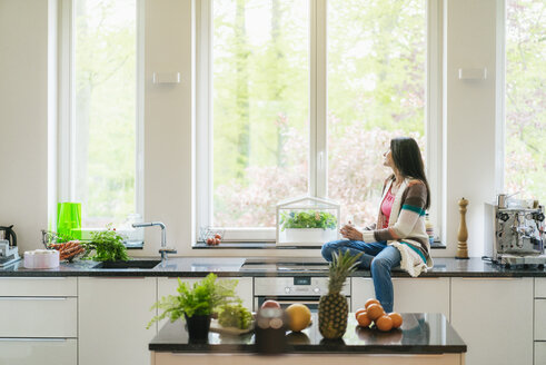 Woman in kitchen looking out of window - JOSF01264