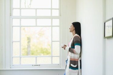 Woman at home looking out of window - JOSF01267