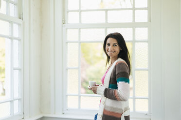 Portrait of smiling woman at the window - JOSF01270
