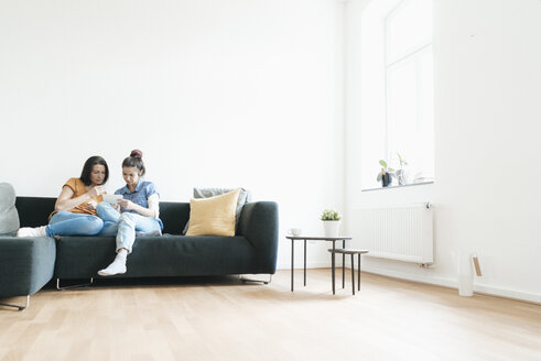 Two women at home sitting on couch looking at photos - JOSF01273