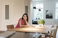 Portrait ofsmiling woman sitting at table at home - JOSF01285