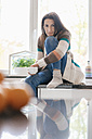 Portrait of woman at home sitting on kitchen counter - JOSF01288