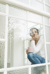 Pensive woman with cup of coffee looking out of window - JOSF01309