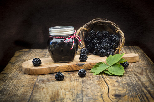 Glass of homemade blackberry jelly and blackberries on wood - LVF06272