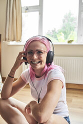Happy young woman with pink hair listening to music - IGGF00065