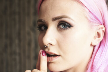 Portrait of young woman with pink hair and piercings - IGGF00068