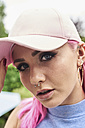 Portrait of young woman with pink hair and piercings wearing cap - IGGF00071