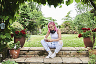 Young woman with pink hair wearing headphones and using cell phone in garden - IGGF00074
