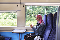 Young woman with pink hair using cell phone while traveling by train - IGGF00080