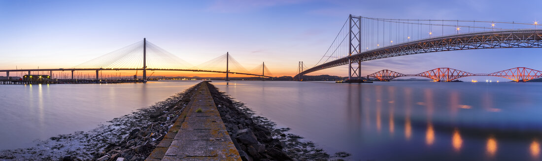 UK, Scotland, Fife, Edinburgh, Firth of Forth estuary, Panorama view from South Queensferry of Forth Bridge, Forth Road Bridge and Queensferry Crossing Bridge at sunset - SMAF00811