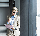 Businesswoman with coffee reading document at the window - UUF11388