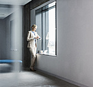 Businesswoman standing at the window - UUF11394