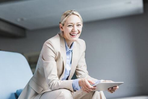 Portrait of happy businesswoman holding tablet - UUF11403