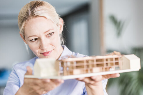 Woman in office holding architectural model - UUF11406