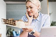 Woman in office holding architectural model - UUF11415
