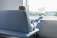 Woman sitting by the window with feet up using tablet - UUF11427