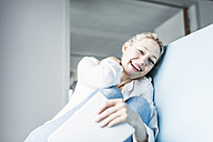 Laughing woman sitting on couch holding tablet - UUF11433
