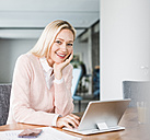 Portrait of smiling businesswoman using tablet in office - UUF11442