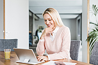 Smiling businesswoman using tablet in office - UUF11445