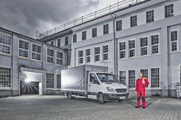Man standing next to delivery van on yard of a building - RHF02019