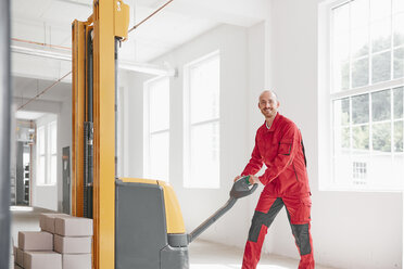 Portrait of smiling man in factory using forklift - RHF02022