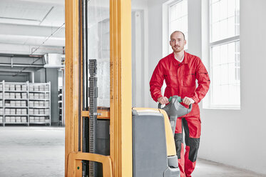 Portrait of man in factory using forklift - RHF02025