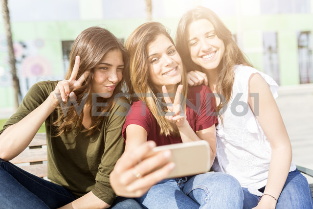 Three happy female friends taking a selfie outdoors - GIOF03006