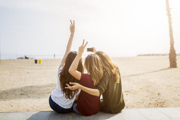 Rear view of three female friends sitting at the beach taking a selfie - GIOF03009