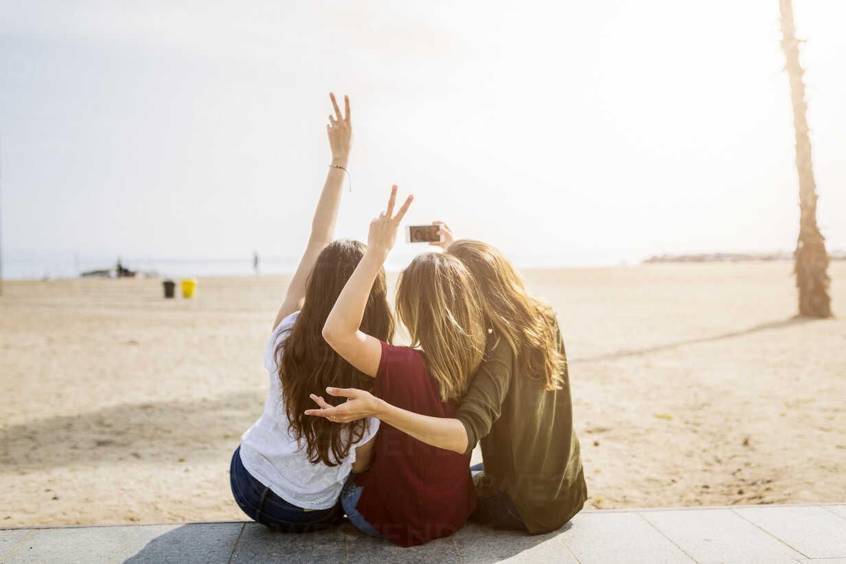 Rear view of three female friends sitting at the beach taking a selfie - GIOF03009 - Giorgio Fochesato/Westend61