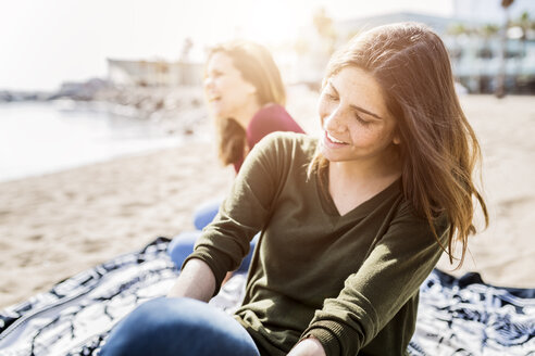 Two happy young women sitting on the beach - GIOF03012