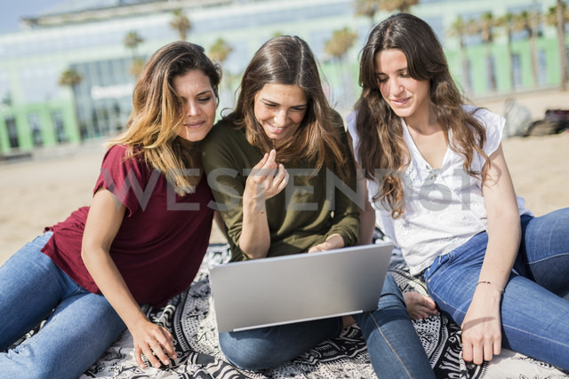 Three happy female friends using a laptop on the beach - GIOF03018