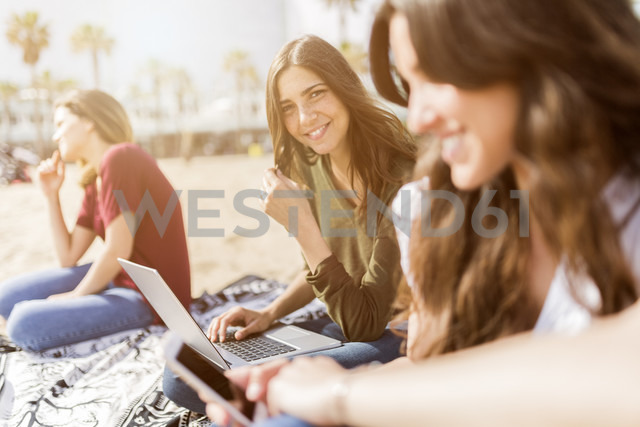 Portrait of smiling young woman with friends on the beach using laptop - GIOF03024