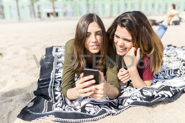 Two happy female friends using cell phone on the beach - GIOF03033