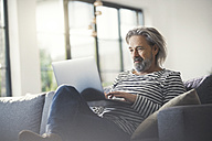 Senior man sitting on couch, using laptop - SBOF00458