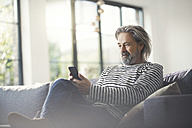 Senior man sitting on couch, using smartphone - SBOF00461