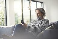 Senior man sitting on couch, using smartphone - SBOF00461